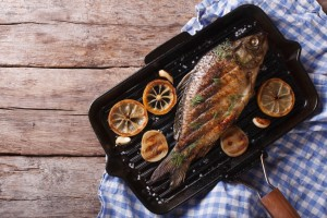 Grilled carp with lemon in a grill pan , horizontal view from above