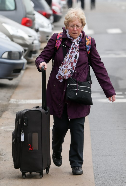 A woman leaves Brussels Airport, in Zaventem, on March 22, 2016, following its evacuation after at least 13 people have been killed by two explosions in the departure hall of Brussels Airport. / AFP / Belga / VIRGINIE LEFOUR / Belgium OUT