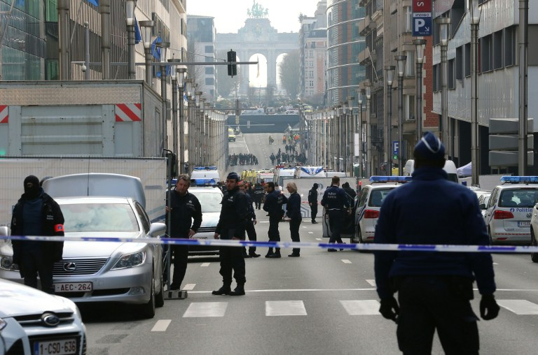 Policemen stand guard near a security perimeter set in the Rue de la Loi near the Maalbeek subway station, in Brussels, on March 22, 2016, after an explosion killed around 10 people, according to spokesman of Brussels' fire brigade A string of explosions rocked Brussels airport and a city metro station on Tuesday, killing at least 13 people, according to media reports, as Belgium raised its terror threat to the maximum level. / AFP / Belga / NICOLAS MAETERLINCK / Belgium OUT