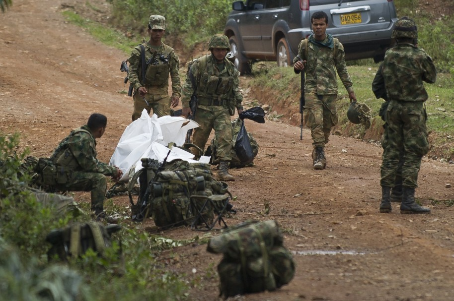Colombian soldiers stand by equipment, weapons and the corpse of one of ten soldiers killed by the Revolutionary Armed Forces of Colombia (FARC) guerrillas, in a rural area of Buenos Aires, department of Cauca, Colombia, on April 15, 2015. Suspected FARC guerrillas killed 10 soldiers and injured 20 others in a pre-dawn attack in western Colombia on Wednesday prompting President Juan Manuel Santos to order a resumption of air strikes against the rebels.   AFP PHOTO/LUIS ROBAYO
