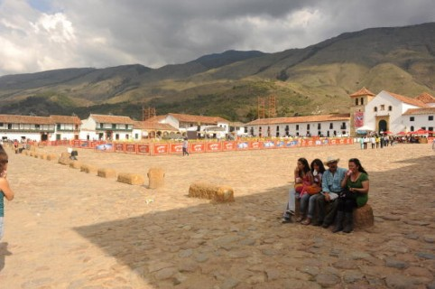 VILLA DE LEYVA, COLOMBIA - DECEMBER 6, 2009:  People sit in Plaza Mayor. Villa de Leyva (sometimes spelled Villa de Leiva) is a colonial town and municipality, in the Boyacá department, part of the subregion of the Ricaurte Province. The town is located some 40 km west of Tunja and has a population of about 4,000 people. Villa de Leyva is considered one of the finest colonial villages of Colombia, and was declared a National Monument in December 17, 1954 to preserve its architecture. It is located in a high altitude valley at 2,144 m altitude where fossils from the Mesozoic and the Cretaceous abound. It was founded in June 12, 1572 by Hernán Suarez de Villalobos and named after the first president of the New Kingdom of Granada, Andrés Díaz Venero de Leyva. Among the main areas of interests are the Plaza Mayor (Main Square) where besides the Church, many restaurants and stores selling some handcrafted art pieces. Most of the streets around the downtown are made of stones, similar to colonial times.  (Photo by Kaveh Kazemi/Getty Images)