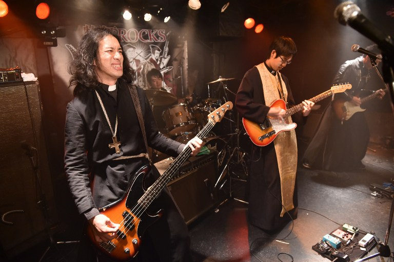 """To go with AFP story Japan-music-religion-lifestyle-offbeat, FEATURE by HARUMI OZAWA This picture taken on September 1, 2015 shows Lutheran pastor Kazuhiro Sekino (L), leader of heavy rock group """"Boxi Rocks"""", performing in Tokyo. Most days, Lutheran pastor Kazuhiro Sekino preaches to his congregation in a soft voice with religious hymns playing in the background of a Tokyo church. But as night falls, he hits a smoky stage criss-crossed with whizzing strobe lights, shedding his pious day job in a battle of the bands against a group of Buddhist monks. AFP PHOTO / Yoshikazu TSUNO / AFP / YOSHIKAZU TSUNO"""