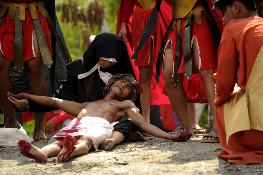 Willy Salvador (L), 59, is lowered to the ground after being nailed to a cross as part of his penitence during a reenactment of the crucifixion of Jesus Christ for Good Friday celebrations ahead of Easter in the village of San Juan, Pampanga, north of Manila on March 25, 2016. Christian devotees were nailed to crosses in the Philippines on March 25 as Asia's Catholic heartland marked Easter with an extreme display of faith.  / AFP / NOEL CELIS