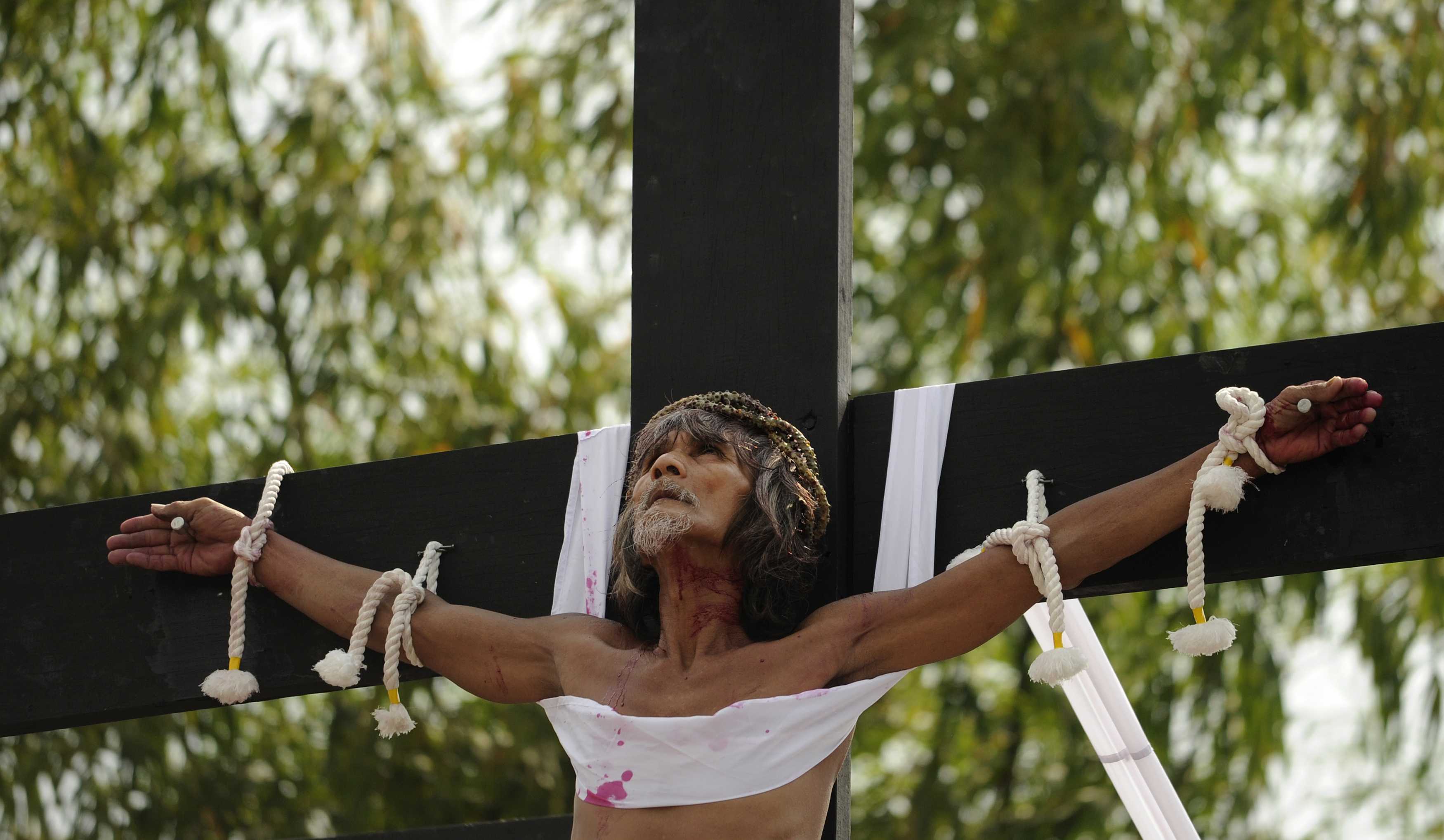 Willy Salvador, 59, hangs from a cross as part of his penitence during a reenactment of the crucifixion of Jesus Christ for Good Friday celebrations ahead of Easter in the village of San Juan, Pampanga, north of Manila on March 25, 2016. Christian devotees were nailed to crosses in the Philippines on March 25 as Asia's Catholic heartland marked Easter with an extreme display of faith. / AFP / NOEL CELIS