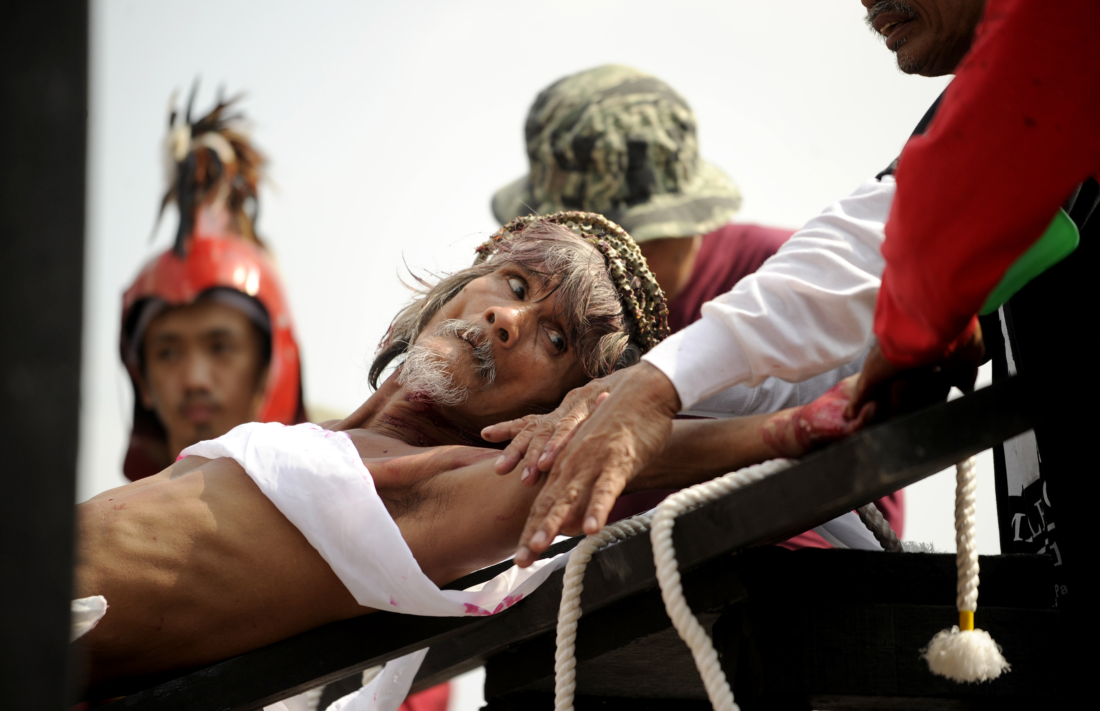 Willy Salvador, 59, is nailed to a cross as part of his penitence during a reenactment of the crucifixion of Jesus Christ for Good Friday celebrations ahead of Easter in the village of San Juan, Pampanga, north of Manila on March 25, 2016. Christian devotees were nailed to crosses in the Philippines on March 25 as Asia's Catholic heartland marked Easter with an extreme display of faith. / AFP / NOEL CELIS