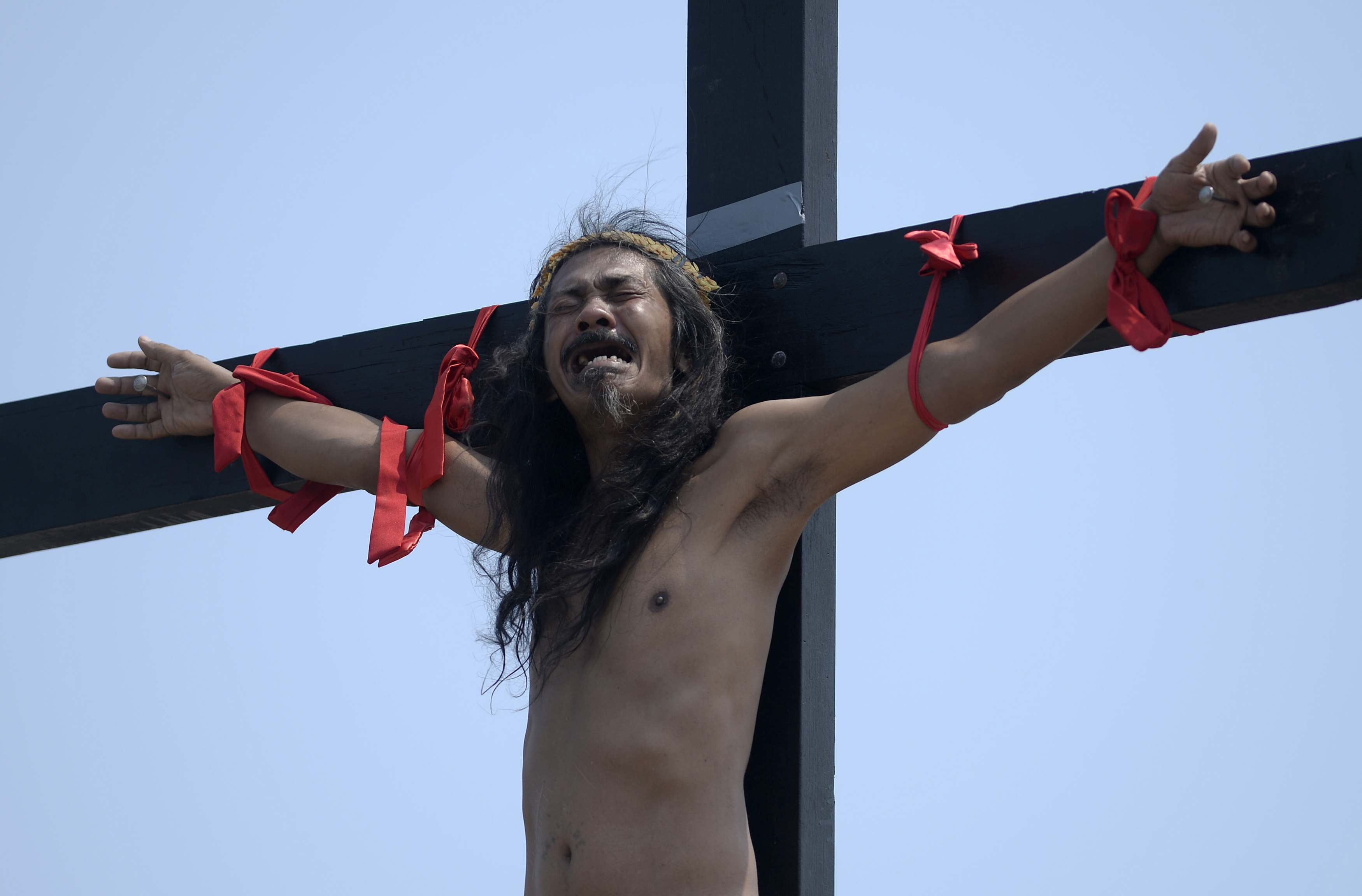 A devotee grimaces as he hangs from a cross after being nailed to it as part of his penitence during the reenactment of the crucifixion of Jesus Christ for Good Friday celebrations ahead of Easter at the village of Cutud near San Fernando, Pampanga province, north of Manila on March 25, 2016. Christian devotees were nailed to crosses in the Philippines on March 25 as Asia's Catholic heartland marked Easter with an extreme display of faith. / AFP / NOEL CELIS