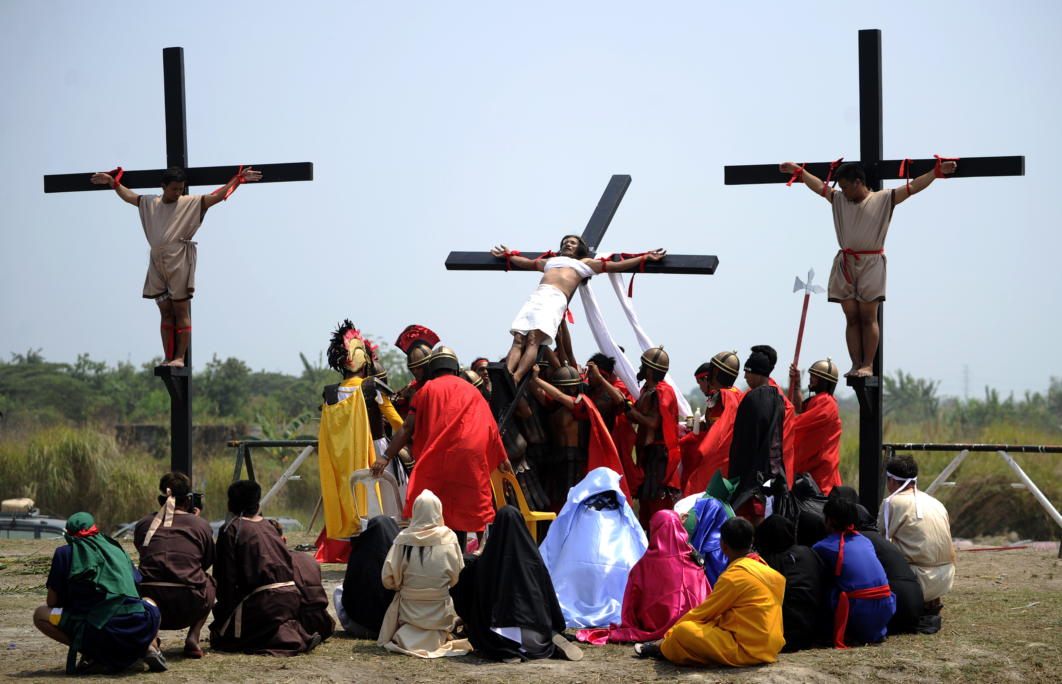 Men dressed as Romans raise up carpenter Ruben Enaje (C), 55, after he was nailed to a cross as part of his penitence during the reenactment of the crucifixion of Jesus Christ during Good Friday celebrations ahead of Easter at the village of Cutud near San Fernando, Pampanga province, north of Manila on March 25, 2016. Christian devotees were nailed to crosses in the Philippines on March 25 as Asia's Catholic heartland marked Easter with an extreme display of faith. / AFP / NOEL CELIS