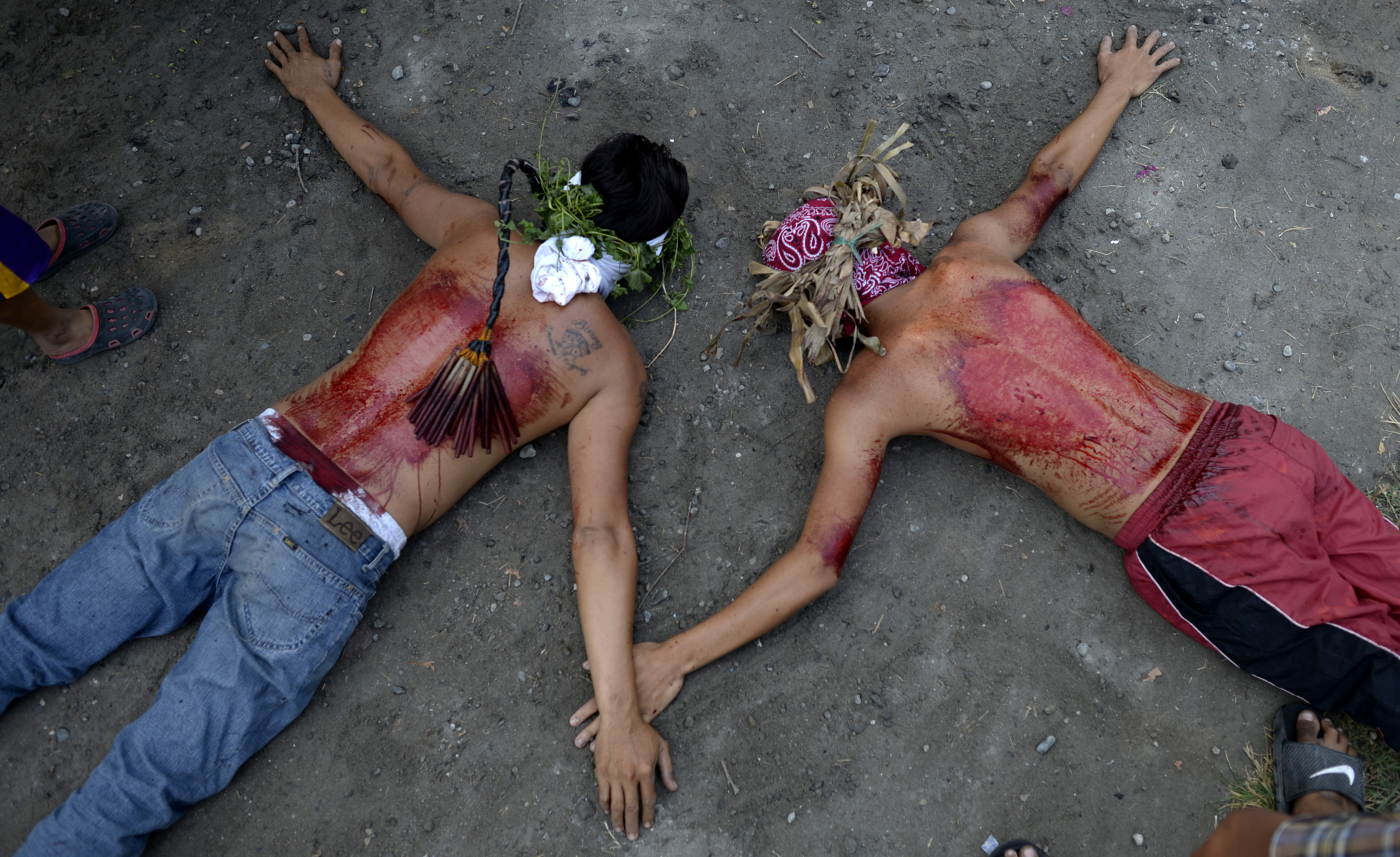 Participants lie on the ground after whipping their bloodied backs with bamboo as part of their penitence during a ceremony reenacting the crucifixion of Jesus Christ for Good Friday celebrations ahead of Easter in the village of San Juan, Pampanga, north of Manila on March 25, 2016. Christian devotees were nailed to crosses in the Philippines on March 25 as Asia's Catholic heartland marked Easter with an extreme display of faith. / AFP / NOEL CELIS