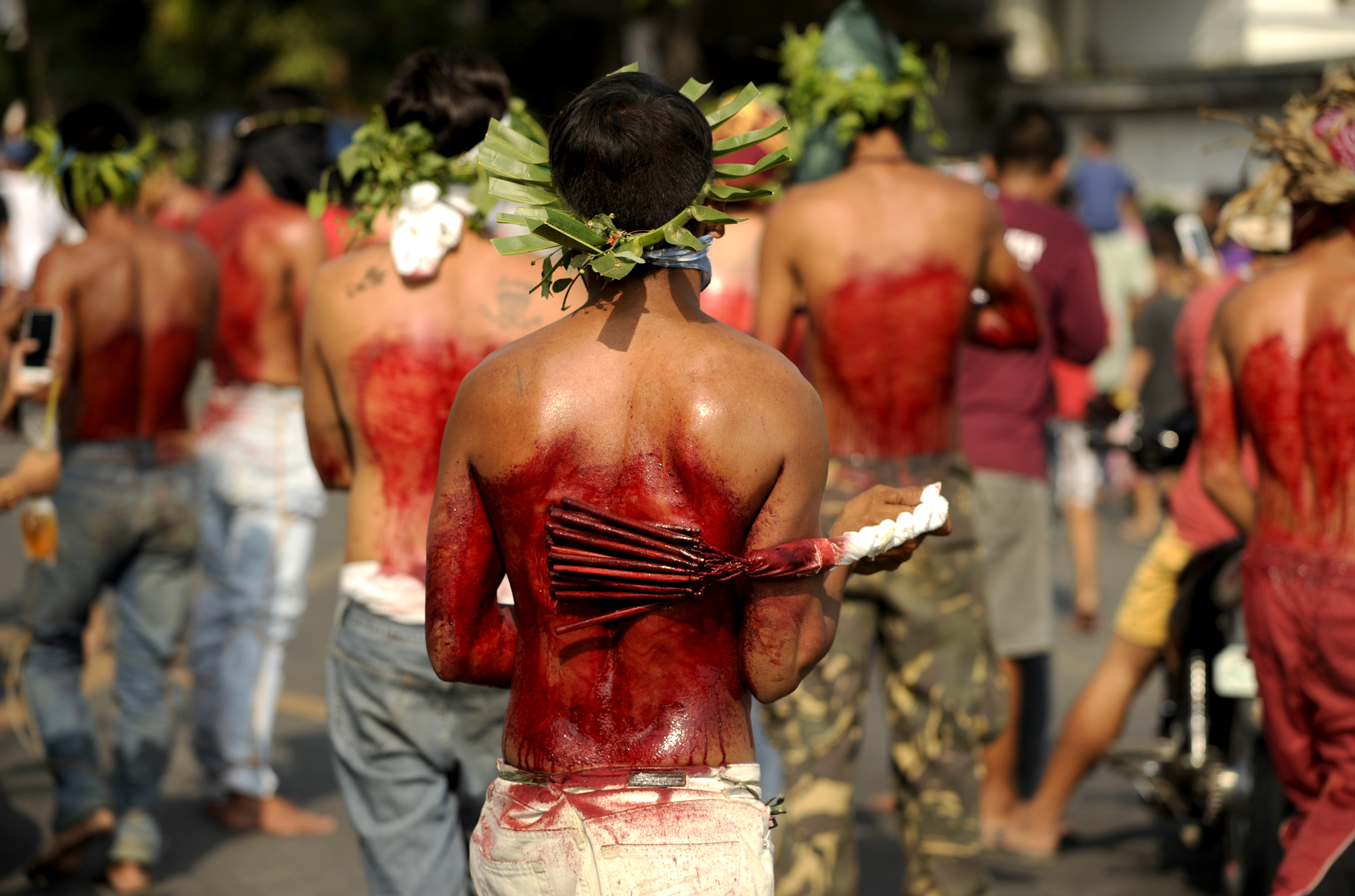 Participants whip their bloodied backs with bamboo as part of their penitence during the re-enactment of the crucifixion of Jesus Christ for Good Friday celebrations ahead of Easter in the village of San Juan, Pampanga, north of Manila on March 25, 2016. Christian devotees were nailed to crosses in the Philippines on March 25 as Asia's Catholic heartland marked Easter with an extreme display of faith. / AFP / NOEL CELIS