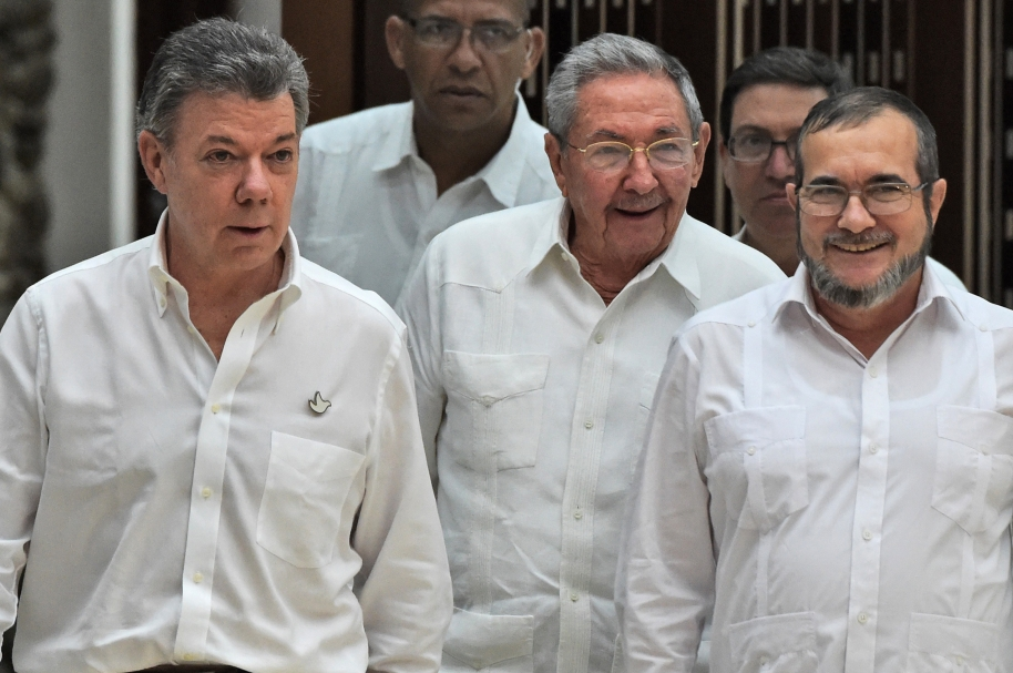 """Cuban President Raul Castro (C), Colombian President Juan Manuel Santos (L) and the head of the FARC guerrilla Timoleon Jimenez, aka Timochenko (R), arrive for a meeting in Havana on September 23, 2015. The Colombian government and FARC rebels announced a key breakthrough in their nearly three-year peace talks Wednesday with the signing of a deal on justice for crimes committed during the five-decade conflict. The deal includes the creation of special courts and a broad amnesty, though this will not cover """"crimes against humanity, serious war crimes"""" and other offenses including kidnappings, extrajudicial executions and sexual abuse, said officials from Cuba and Norway, the guarantors in the talks. AFP PHOTO / Rodrigo ARANGUA"""