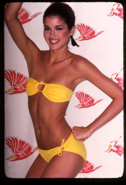 Portrait of American fashion model Janice Dickinson as she poses in a yellow, two-piece bathing suit, with one hand on her hip and the other above her head, late 1970s. (Photo by Anthony Barboza/Getty Images)