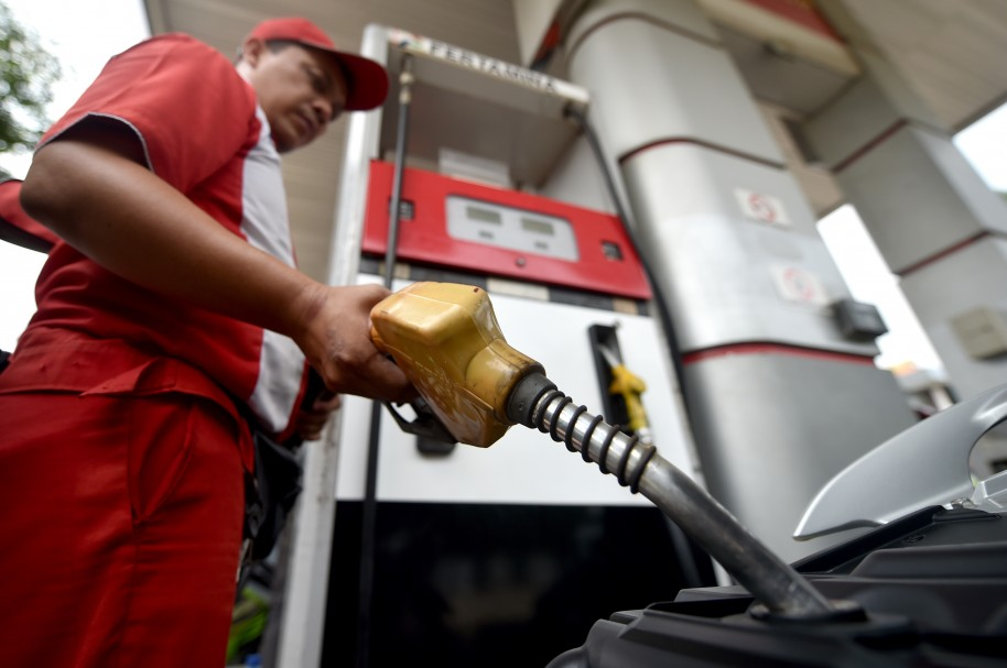 A petrol station employee fills up a vehicle with subsidized-fuel in Jakarta on November 14, 2014. Indonesia's central bank kept its key interest rate steady despite slowing growth, ahead of an expected fuel price hike by the new government that will likely push up inflation. AFP PHOTO / Bay ISMOYO