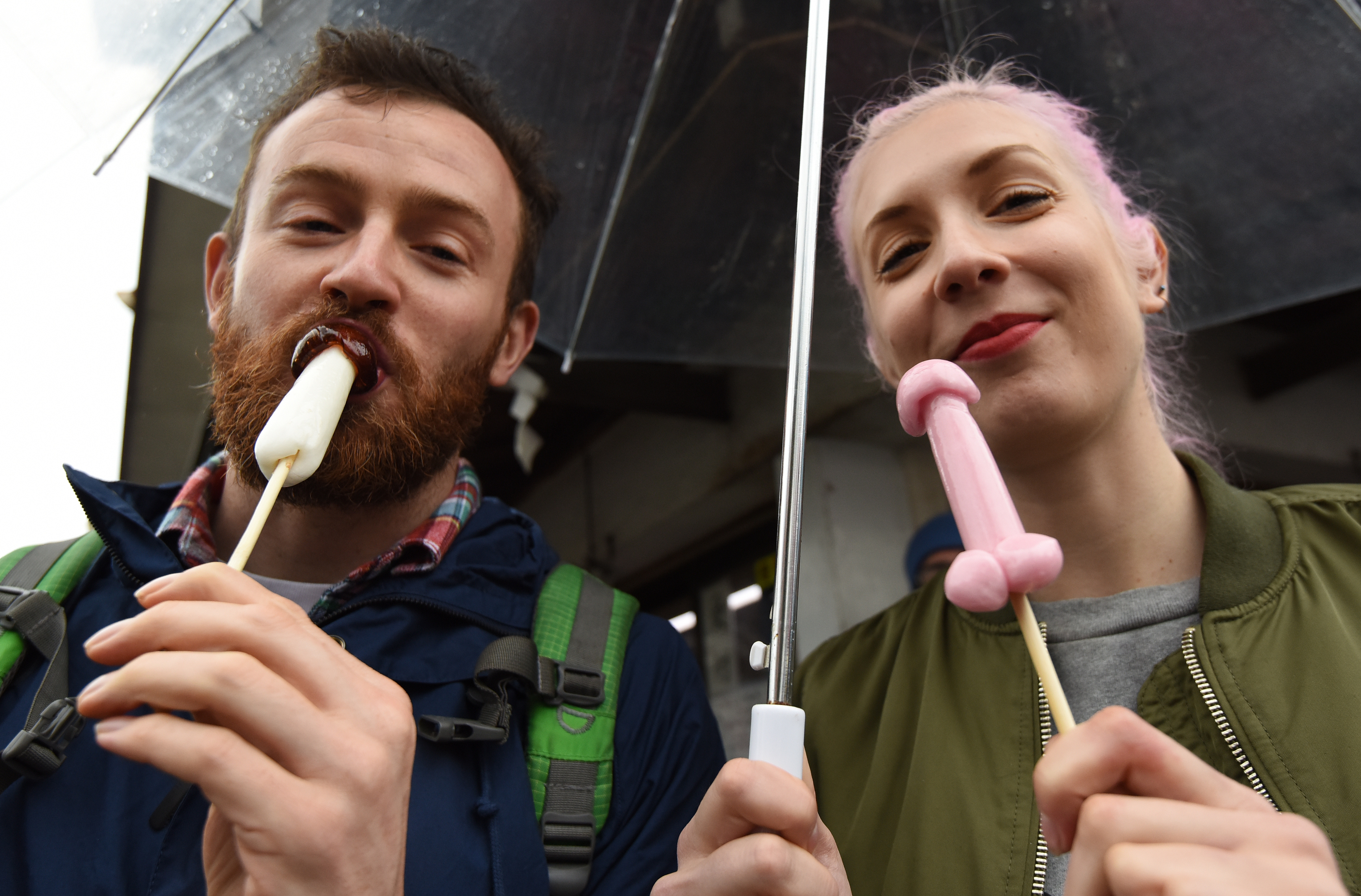 A couple hold candy in the shape of phalluses at the Wakamiya Hachimangu Shrine during the Kanamara Festival in Kawasaki, a suburb of Tokyo on April 3, 2016. More than 20,000 people gathered to enjoy the annual festival which Shinto believers carry giant phalluses through the streets. / AFP / TORU YAMANAKA