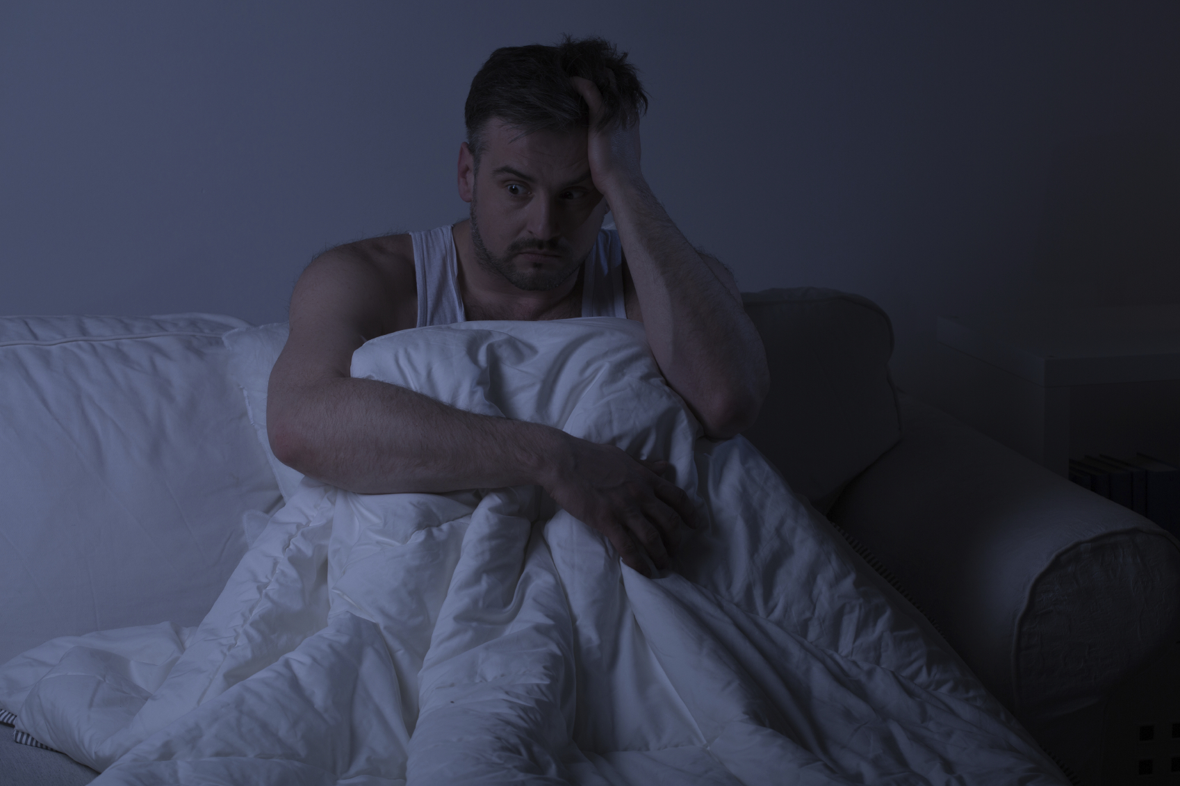 Mature man with insomnia sitting in the bed