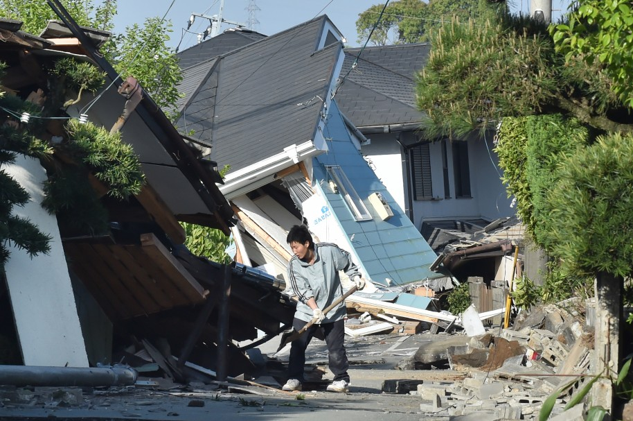 A man clears away debris of a broken wall in Mashiki, Kumamoto prefecture on April 16, 2016.   A powerful earthquake hit southern Japan early April 16, authorities said, sending panicked residents out of their homes in a region where nerves were already frayed by a swarm of strong shaking. / AFP PHOTO / KAZUHIRO NOGI