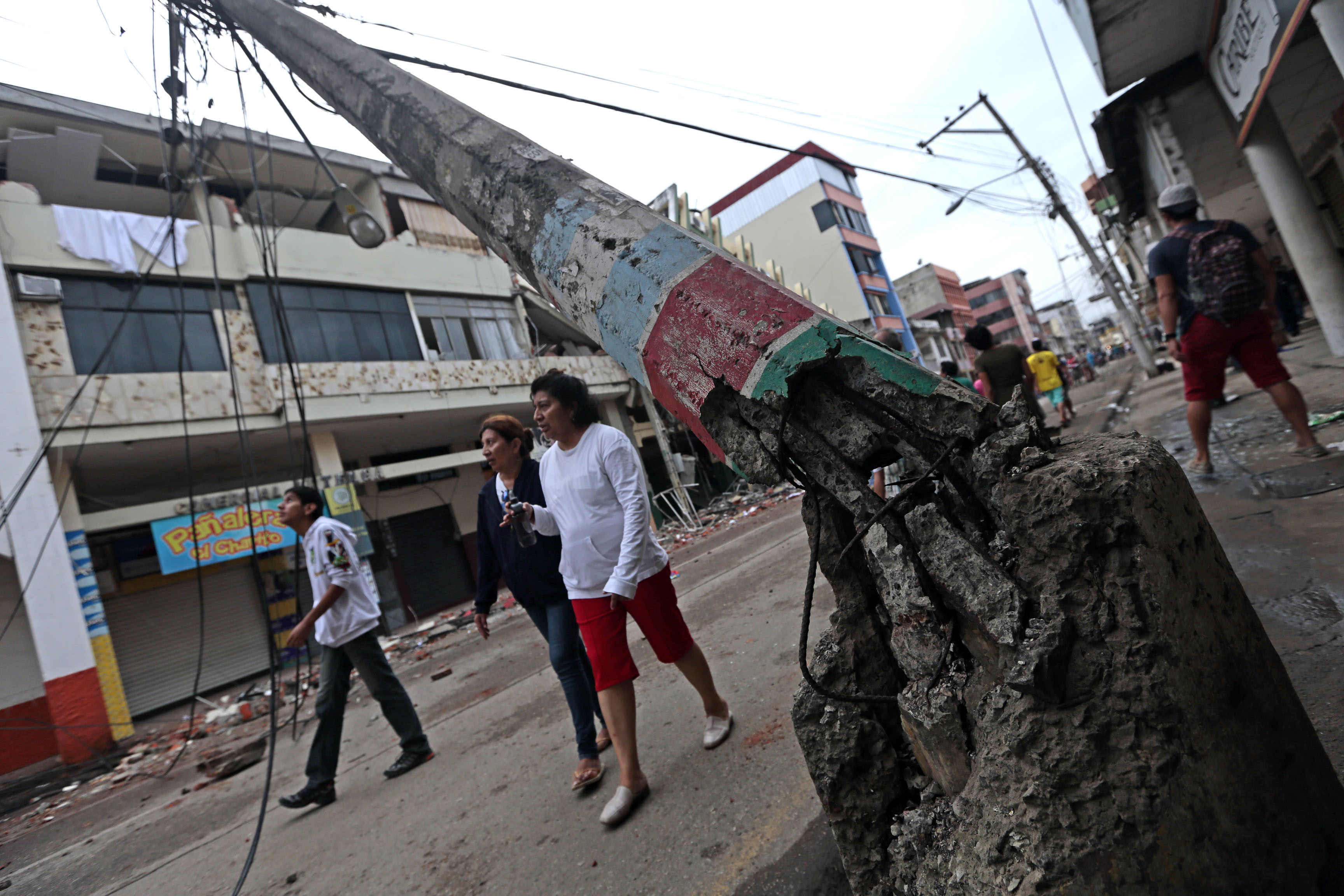 People walk along a street after a 7.8-magnitude quake in Portoviejo, Ecuador on April 17, 2016. At least 77 people were killed when a powerful earthquake struck Ecuador, destroying buildings and a bridge and sending terrified residents scrambling from their homes, authorities said Sunday. / AFP PHOTO / JUAN CEVALLOS