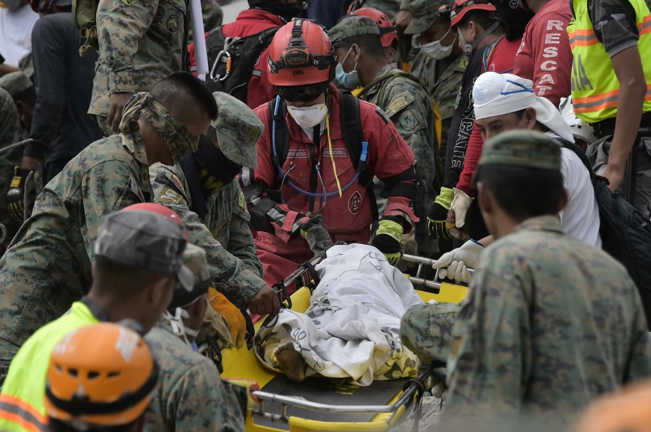 Rescuers recover the body of a dead child from the rubble in Pedernales, one of Ecuador's worst-hit towns, on April 18, 2016 two days after a 7.8-magnitude quake hit the country. Rescuers and desperate families clawed through the rubble Monday to pull out survivors of an earthquake that killed 350 people and destroyed towns in a tourist area of Ecuador. / AFP PHOTO / RODRIGO BUENDIA