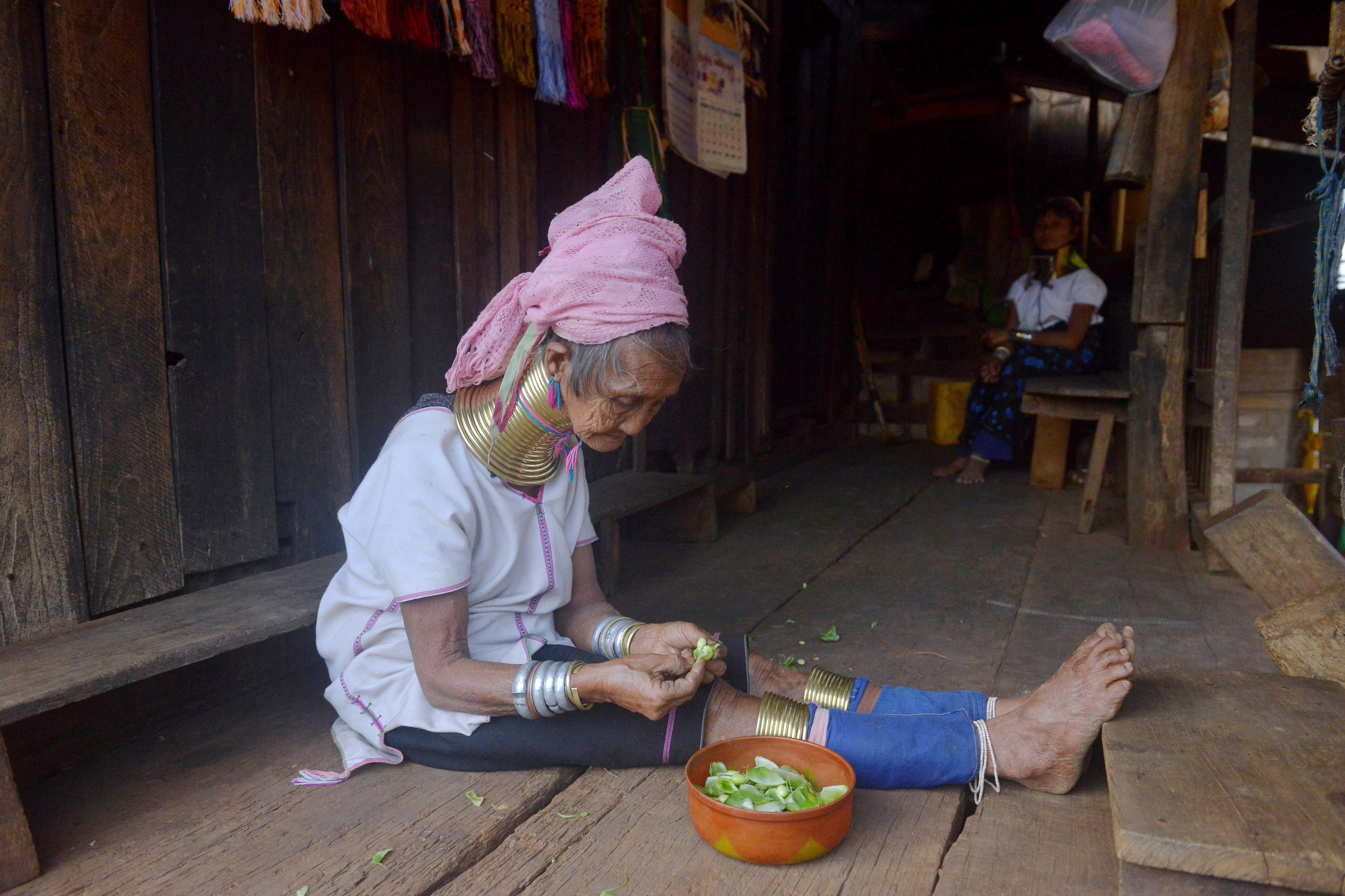 """In this picture taken on March 6, 2016 Monu, 76 year old Kayan tribeswoman, prepares food in her home wearing a stack of bronze neck coils, the statuesque sign of beauty of her Kayan tribe at Panpet village located in Demoso township in Kayah state, central Myanmar. For years Kayan women and girls have been driven across the border by poverty and conflict to pose in holidaymakers' pictures in purpose-built Thai villages, decried by campaigners as """"human zoos"""" that exploit a vulnerable minority. / AFP PHOTO / PHYO HEIN KYAW / TO GO WITH AFP STORY: Myanmar-Thailand-tourism-leisure-culture, FEATURE by Phyo Hein Kyaw"""