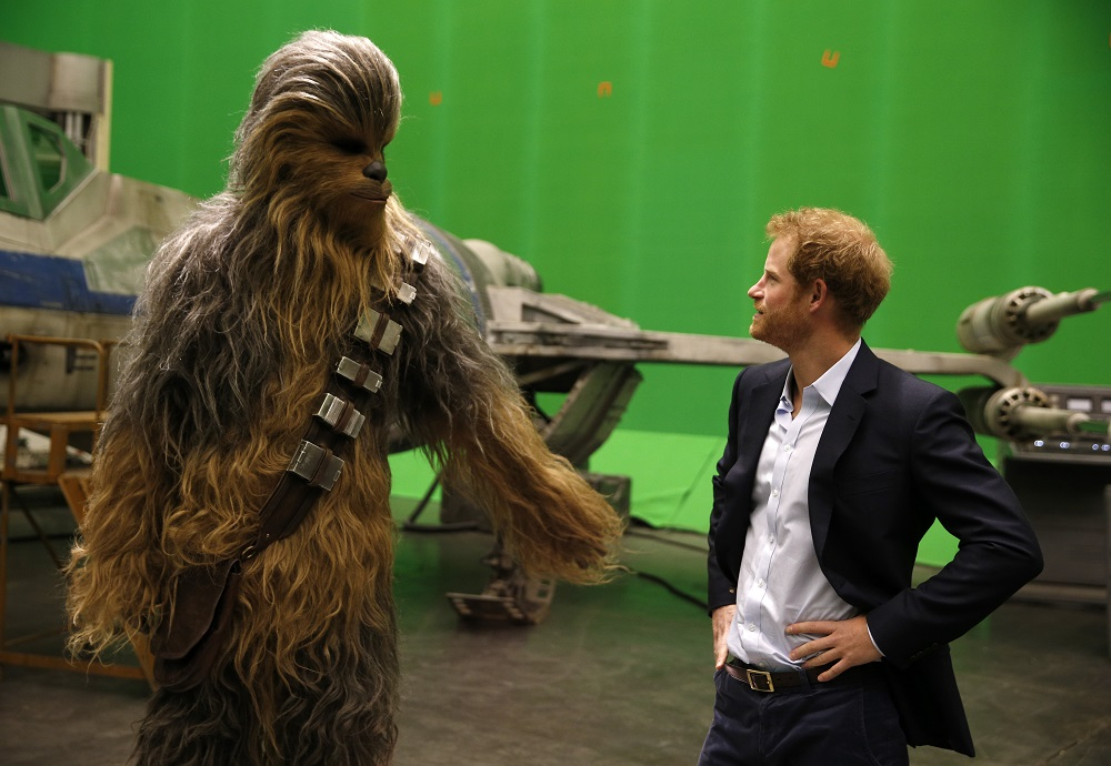 Britain's Prince Harry (R) meets Chewbacca during a visit to the Star Wars film set at Pinewood Studios near Iver Heath, west of London April 19, 2016. Prince William and Prince Harry are touring Pinewood to visit the production workshops and meet the creative teams working behind the scenes on the Star Wars films. / AFP PHOTO / ADRIAN DENNIS
