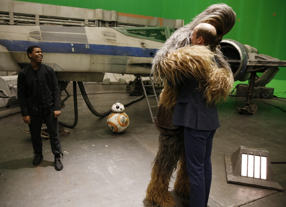 Britain's Prince William, Duke of Cambridge (R) is hugged by Chewbacca as British actor John Boyega smiles during a tour of the Star Wars sets at Pinewood studios in Iver Heath, west of London on April 19, 2016. Prince William and Prince Harry are touring Pinewood to visit the production workshops and meet the creative teams working behind the scenes on the Star Wars films. / AFP PHOTO / ADRIAN DENNIS