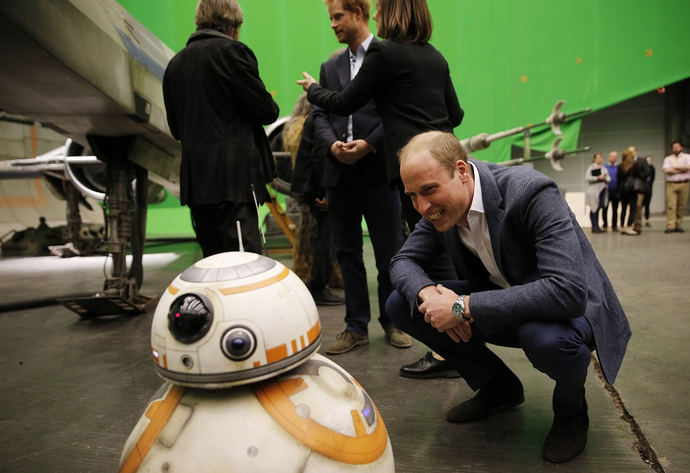 Britain's Prince William, Duke of Cambridge smiles at BB-8 droid during a tour of the Star Wars sets at Pinewood studios in Iver Heath, west of London on April 19, 2016. Prince William and Prince Harry are touring Pinewood to visit the production workshops and meet the creative teams working behind the scenes on the Star Wars films. / AFP PHOTO / ADRIAN DENNIS
