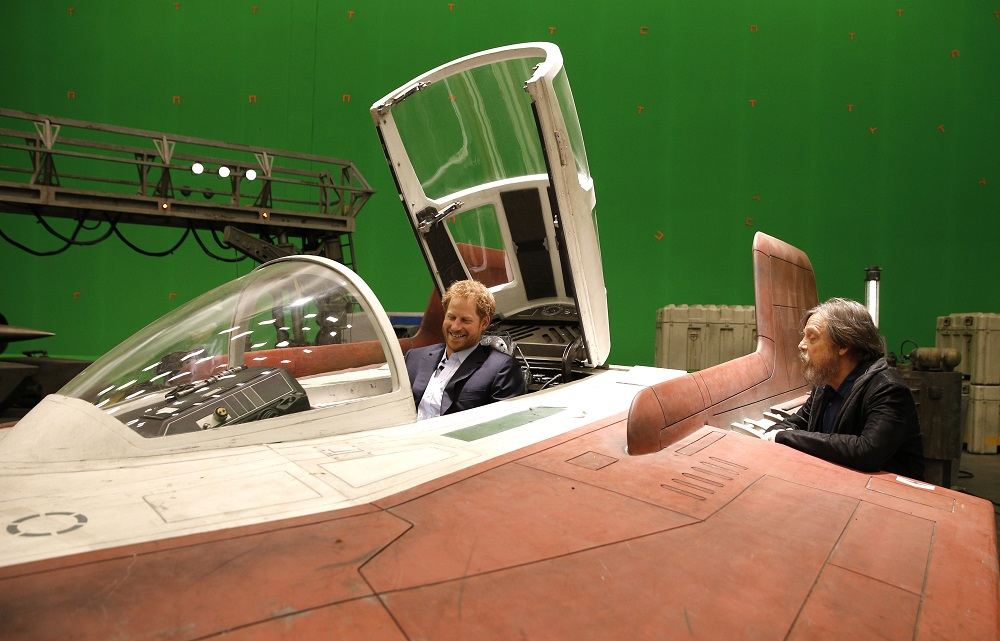 Britain's Prince Harry sits in an A-wing fighter as he talks with US actor Mark Hamill during a tour of the Star Wars sets at Pinewood studios in Iver Heath, west of London on April 19, 2016. Prince William, Duke of Cambridge and Prince Harry are touring Pinewood to visit the production workshops and meet the creative teams working behind the scenes on the Star Wars films. / AFP PHOTO / ADRIAN DENNIS