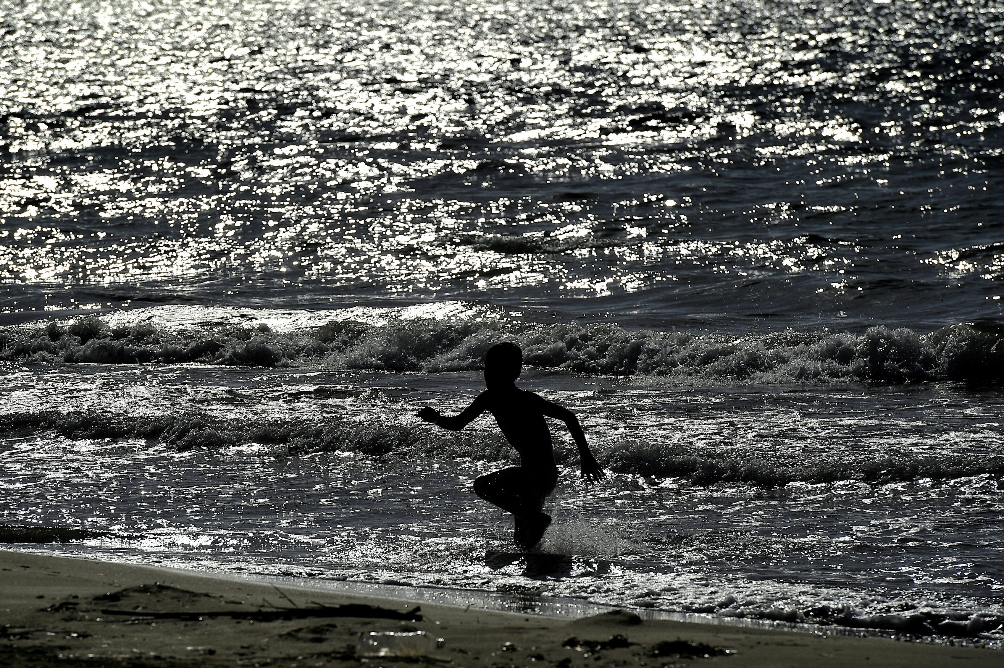 TO GO WITH AFP STORY BY JOHN HADOULIS A child runs on the beach in Myrsini on April 20, 2016, a few metres away from a summer resort sheltering nearly 350 Syrian refugees under the care of a Syria-born mayor, the first naturalised ex-migrant elected to office in Greece. The LM Village resort, partly owned by the local municipality of Kyllini, some 280 kilometres (170 miles) west of Athens, had previously been abandoned for years and extensively looted, a side-effect of the economic crisis gripping Greece since 2010. Each of its small apartments now houses two families with children, the youngest of which was born in a nearby hospital a few days ago. / AFP PHOTO / ARIS MESSINIS