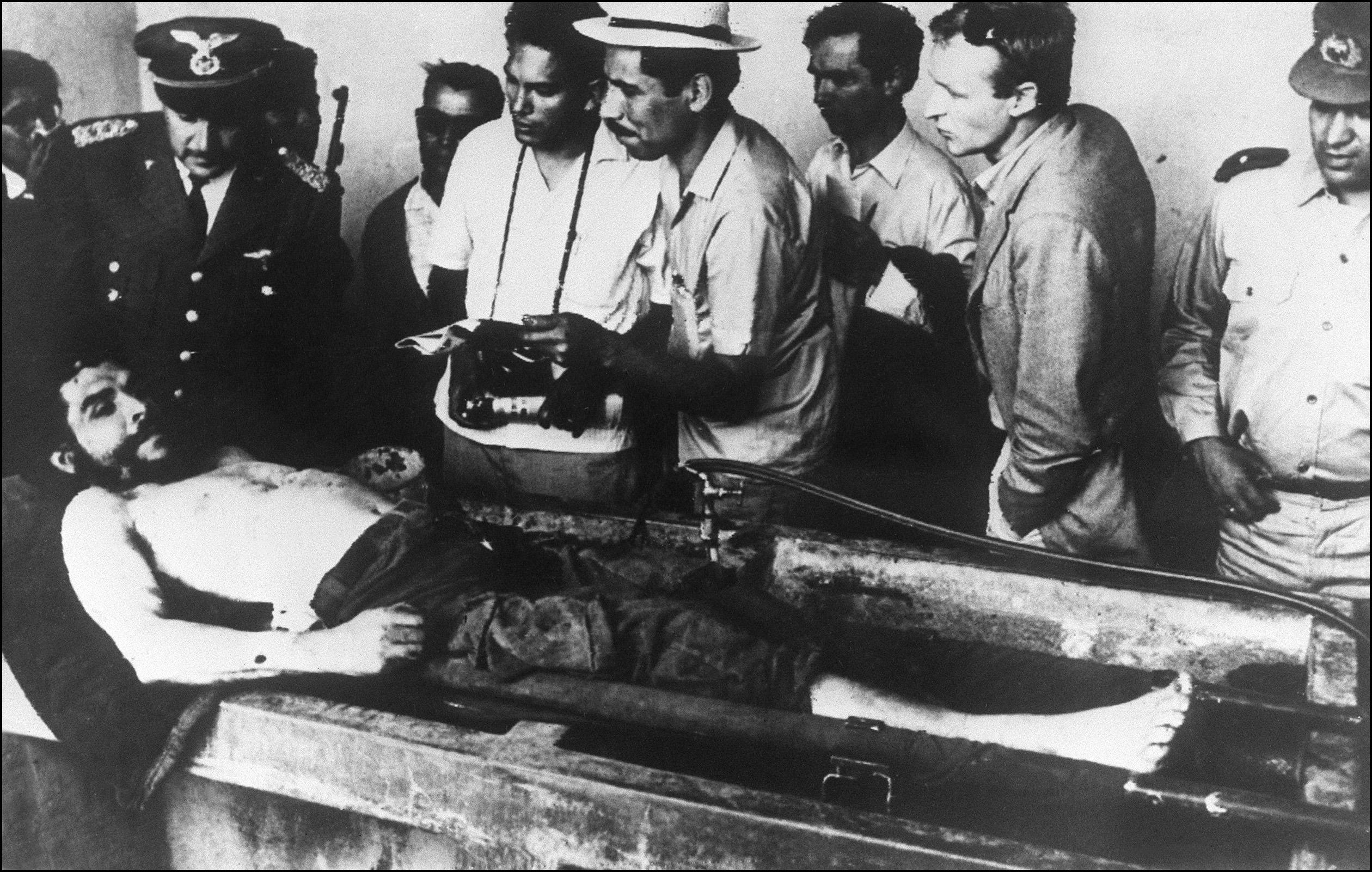 "The body of Ernesto ""Che"" Guevara, the Argentine-born hero of Latin American revolutionaries, surrounded by Bolivian army officers and journalists, is on public display in the makeshift morgue 10 October 1967 in Vallegrande. He was captured 08 October and shot dead 09 October by Bolivian forces. ""Che"" Guevara, the 39-year-old firebrand, was formerly the confident of Cuban leader Fidel Castro. In 1965 he left Cuba to establish guerrilla groups in Latin America.# Des militaires boliviens présentent le 10 octobre 1967 à Vallegrande à la presse internationale le corps d'Ernesto ""Che"" Guevara, d'origine argentine. Après avoir pris part à la Révolution cubaine et lancé à partir de 1965 des foyers insurrectionnels en Amérique Latine, il a été pourchassé par l'armée bolivienne à l'aide des agents de la CIA. Capturé le 08 octobre, il fut exécuté le lendemain et enterré dans le secret. (FILM) AFP PHOTO / AFP PHOTO"
