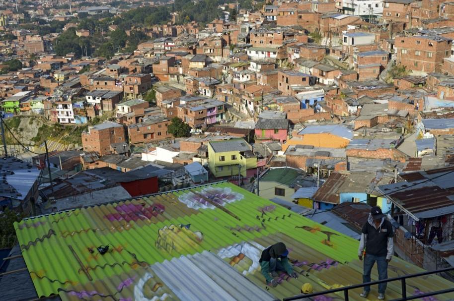 Un hombre pinta el tejado de una casa, en una comuna de Medellín