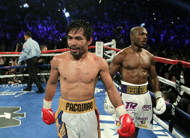 Manny Pacquiao (L) smiles as he walks back to his corner followed by Timothy Bradley Jr. at the end of their fight at the MGM Grand Arena on April 9, 2016 in Las Vegas, Nevada. Pacquio won a 12 round unanimous decision to capture the WBO International Welterweight Title. / AFP PHOTO / John GURZINSKI