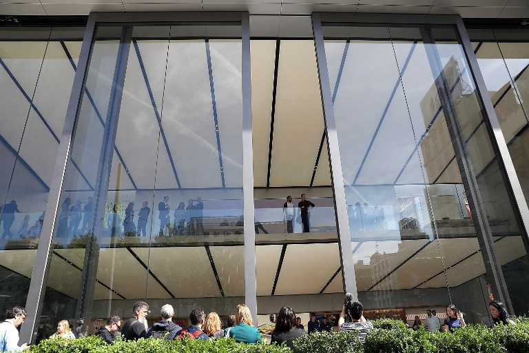 "SAN FRANCISCO, CA - MAY 19: Members of the media look on as 42-foot tall sliding glass doors open during a press preview at the new flagship Apple Store on May 19, 2016 in San Francisco, California. Apple is preparing to open its newest flagship store in San Francisco's Union Square on Saturday May 21. The new store features new design elements as well as community programs including the ""genius grove"" where where customers can get support under a canopy of local trees and ""the plaza"" a public space that will be open 24 hour a day. Visitors will enter the store through 42-foot tall sliding glass doors. Justin Sullivan/Getty Images/AFP"