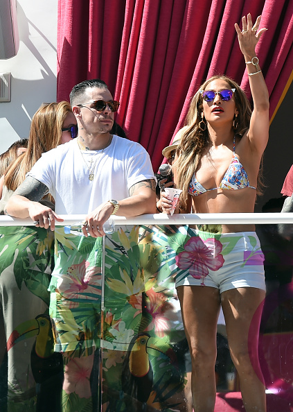 "LAS VEGAS, NV - MAY 29: Choreographer/dancer Beau ""Casper"" Smart (L) looks on as singer/actress Jennifer Lopez gestures to guests while hosting the ""Carnival Del Sol"" pool party at Drai's Beach Club - Nightclub at The Cromwell Las Vegas on May 29, 2016 in Las Vegas, Nevada. (Photo by Ethan Miller/Getty Images)"