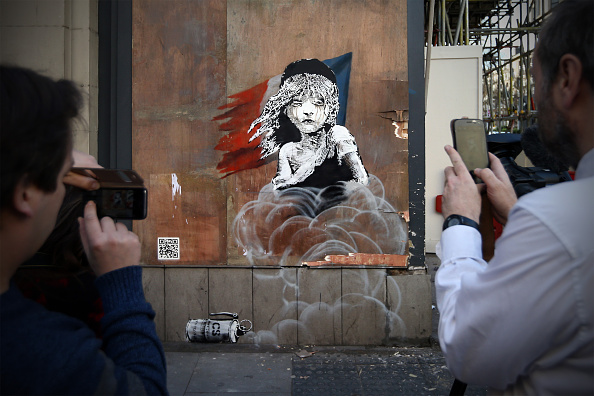 LONDON, ENGLAND - JANUARY 25: People photograph a Banksy artwork opposite the French embassy on January 25, 2016 in London, England. The graffiti, which depicts a young girl from the musical Les Miserables with tears in her eyes as CS gas moves towards her, criticises the use of teargas in the 'Jungle' migrant camp in Calais. (Photo by Carl Court/Getty Images)