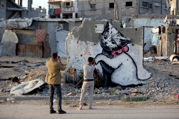 BEIT HANOUN, GAZA - FEBRUARY 27: Graffitis are seen on a wall of a building, drawn by British artist Banksy in Beit Hanoun, Gaza on February 27, 2015. Famous British artist Banksy visited Gaza and drew graffiti on the walls of houses in Beit Hanoun destroyed in Israel's recent attacks on Gaza. (Photo by Mustafa Hassona/Anadolu Agency/Getty Images)