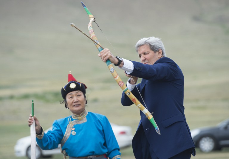 US Secretary of State John Kerry shoots a bow and arrow as he participates in a Naadam ceremony, a competition which traditionally includes horse racing, Mongolian wrestling and archery, in Ulan Bator, Mongolia on June 5, 2016. Kerry arrived in Mongolia on June 5, the latest senior US official to make the trip to the mineral-rich country neighboured by Russia and China. / AFP PHOTO / POOL / SAUL LOEB