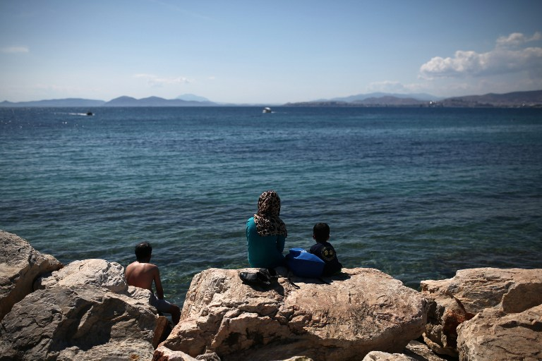 Migrants sit facing the sea near the former international airport in Athens, currently used as a temporary camp for migrants and refugees, on June 5, 2016. Problems in implementing a controversial EU-Turkey deportation deal have created a bottleneck of some 8,500 migrants on Greek islands, where brawls in overcrowded camps are common. / AFP PHOTO / ANGELOS TZORTZINIS