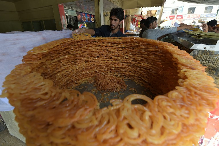 Pakistani bakers prepare Iftar food for Muslims breaking their fast on the first day of fasting month of Ramadan, at a market in Islamabad on June 7, 2016. Islam's holy month of Ramadan is celebrated by Muslims worldwide marked by fasting, abstaining from foods, sex and smoking from dawn to dusk for soul cleansing and strengthening the spiritual bond between them and the Almighty. / AFP PHOTO / AAMIR QURESHI