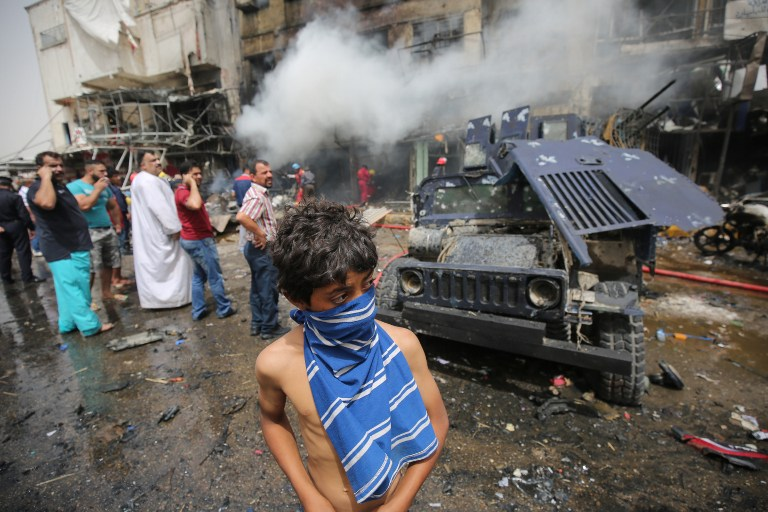 Iraqis check the scene of a car bomb attack in the mostly Shiite neighbourhood of Baghdad Jadida in the Iraqi capital on June 9, 2016. A suicide car bomb attack near a military base north of Baghdad and another blast near a market in the Iraqi capital killed at least 18 people, police said. / AFP PHOTO / AHMAD AL-RUBAYE
