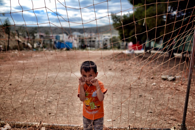 A boy looks on behind a net at the refugee camp of Schisto on June 8, 2016 in Athens. The Schisto camp, which accomodates some 1,700 migrants of all ages, the vast majority of them from Afghanistan, is an open facility where people who are assigned there are free to come and go. / AFP PHOTO / ARIS MESSINIS