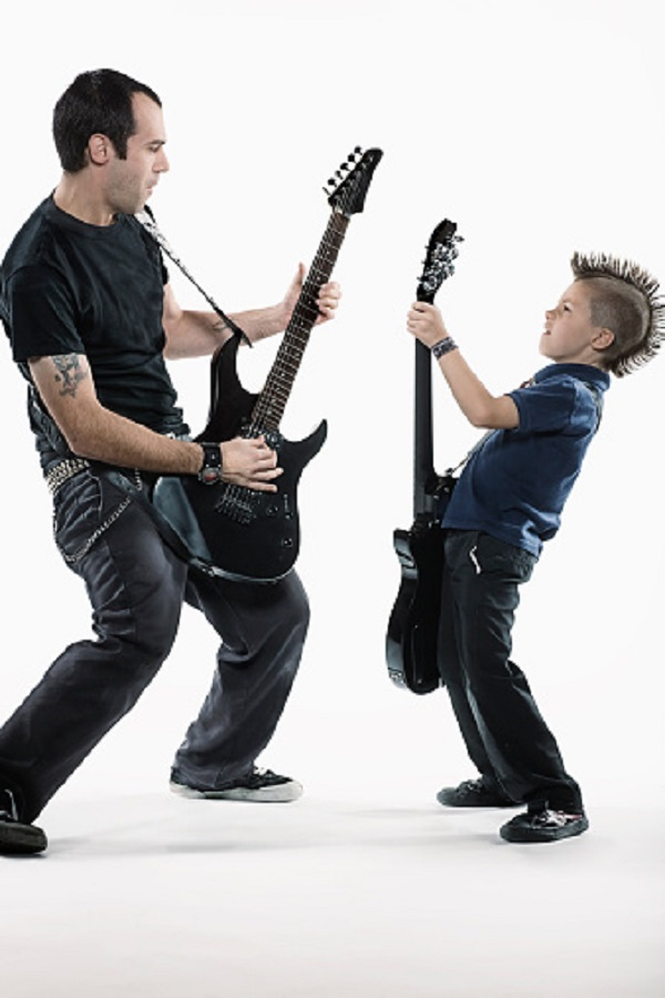 Father and son (8-10) playing guitars