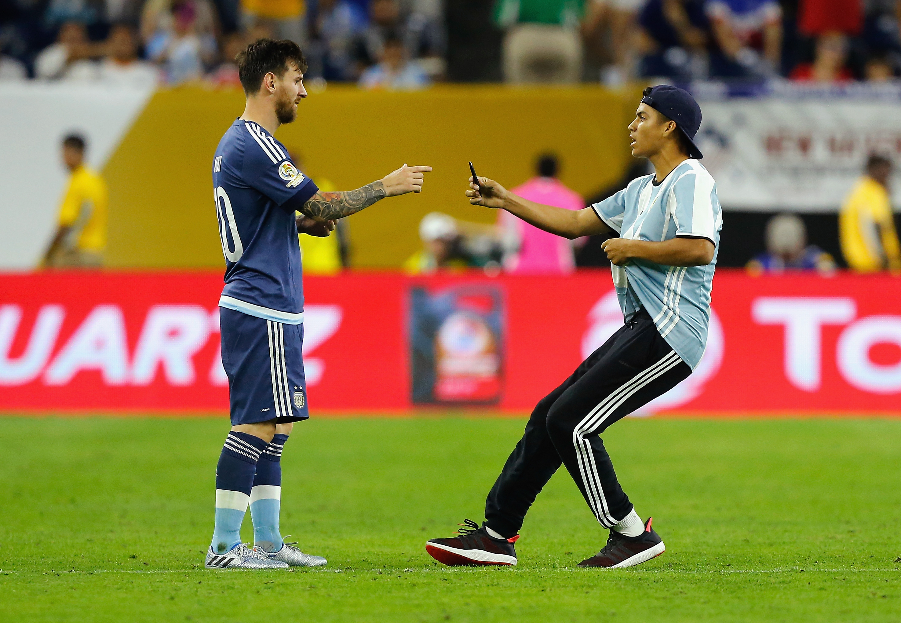 HOUSTON, TX - JUNE 21: Lionel Messi #10 of Argentina interacts with a fan who ran onto the field prior to the start of the second half during a 2016 Copa America Centenario Semifinal match between Argentina and the United States at NRG Stadium on June 21, 2016 in Houston, Texas. Bob Levey/Getty Images/AFP