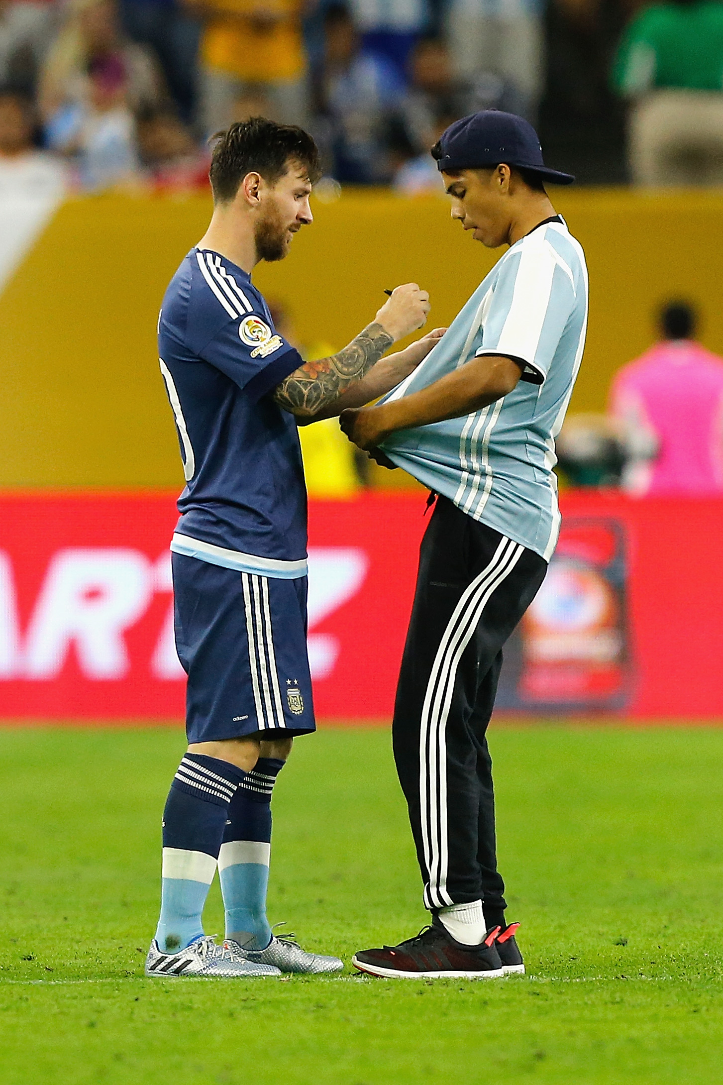 HOUSTON, TX - JUNE 21: Lionel Messi #10 of Argentina autographs the shirt of a fan who ran onto the field prior to the start of the second half during a 2016 Copa America Centenario Semifinal match between Argentina and the United States at NRG Stadium on June 21, 2016 in Houston, Texas. Bob Levey/Getty Images/AFP