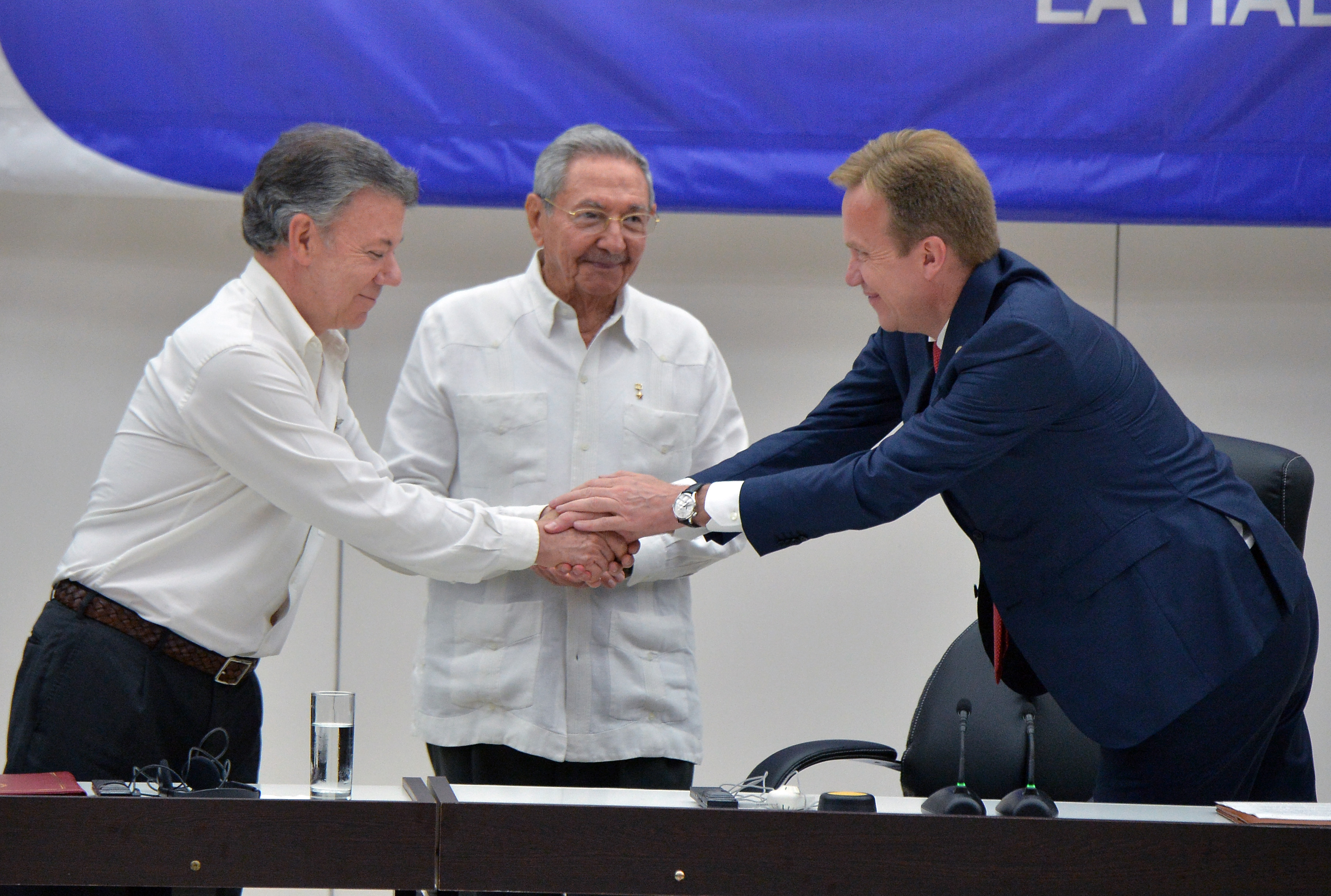 Colombia's President Juan Manuel Santos (L) shakes hands with Norway's Foreign Minister Borge Brende, as Cuban President Raul Castro (C) looks on during the signing of the ceasefire between the Colombian government and the FARC guerrilla, in Havana on June 23, 2016. Colombia's government and the FARC guerrilla force signed a definitive ceasefire Thursday, taking one of the last crucial steps toward ending Latin America's longest civil war. / AFP PHOTO / ADALBERTO ROQUE
