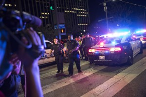Bystanders stand near pollice baracades following the sniper shooting in Dallas on July 7, 2016. A fourth police officer was killed and two suspected snipers were in custody after a protest late Thursday against police brutality in Dallas, authorities said. One suspect had turned himself in and another who was in a shootout with SWAT officers was also in custody, the Dallas Police Department tweeted. / AFP PHOTO / Laura Buckman