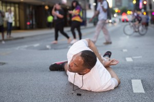 """A man lays on the ground after yelling """"Don't shoot me"""" at police during a rally in Dallas, Texas, on Thursday, July 7, 2016 to protest the deaths of Alton Sterling and Philando Castile. Black motorist Philando Castile, 32, a school cafeteria worker, was shot at close range by a Minnesota cop and seen bleeding to death in a graphic video shot by his girlfriend that went viral Thursday, the second fatal police shooting to rock America in as many days. / AFP PHOTO / Laura Buckman"""