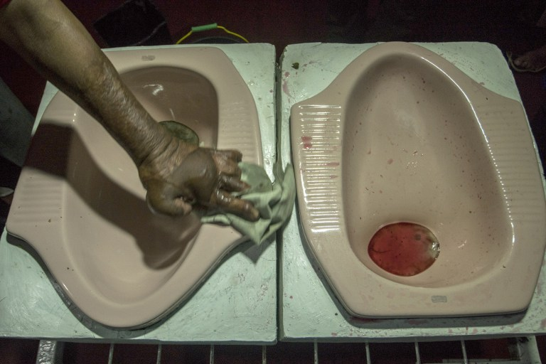 """This picture taken on July 16, 2016 shows a worker cleaning up a squat toilet display from where customers ate a meal at the """"Jamban Cafe"""" in the city of Semarang on Java island, a small eatery where a handful of diners sit on upright toilets around a table where food is served in two squat toilets. The toilet-themed cafe where customers dine on meatballs floating in soup-filled latrines may not be everyone's idea of haute cuisine, but Indonesians are flocking to become privy to the latest lavatorial trend. / AFP PHOTO / SURYO WIBOWO"""
