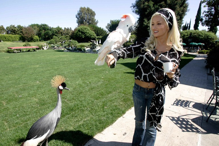"Holly, one of the three girlfriends of Playboy Enterprises CEO Hugh Hefner plays with a perrot during a guided tour of the mansion in Los Angeles, CA 23 August 2006. Hefner called journalists to promote the premiere in France of the series ""The Girl Next Door"", a reality show that introduces the viewer into the daily life of Hefner and his three girlfriends. AFP PHOTO / HECTOR MATA / AFP PHOTO / HECTOR MATA"