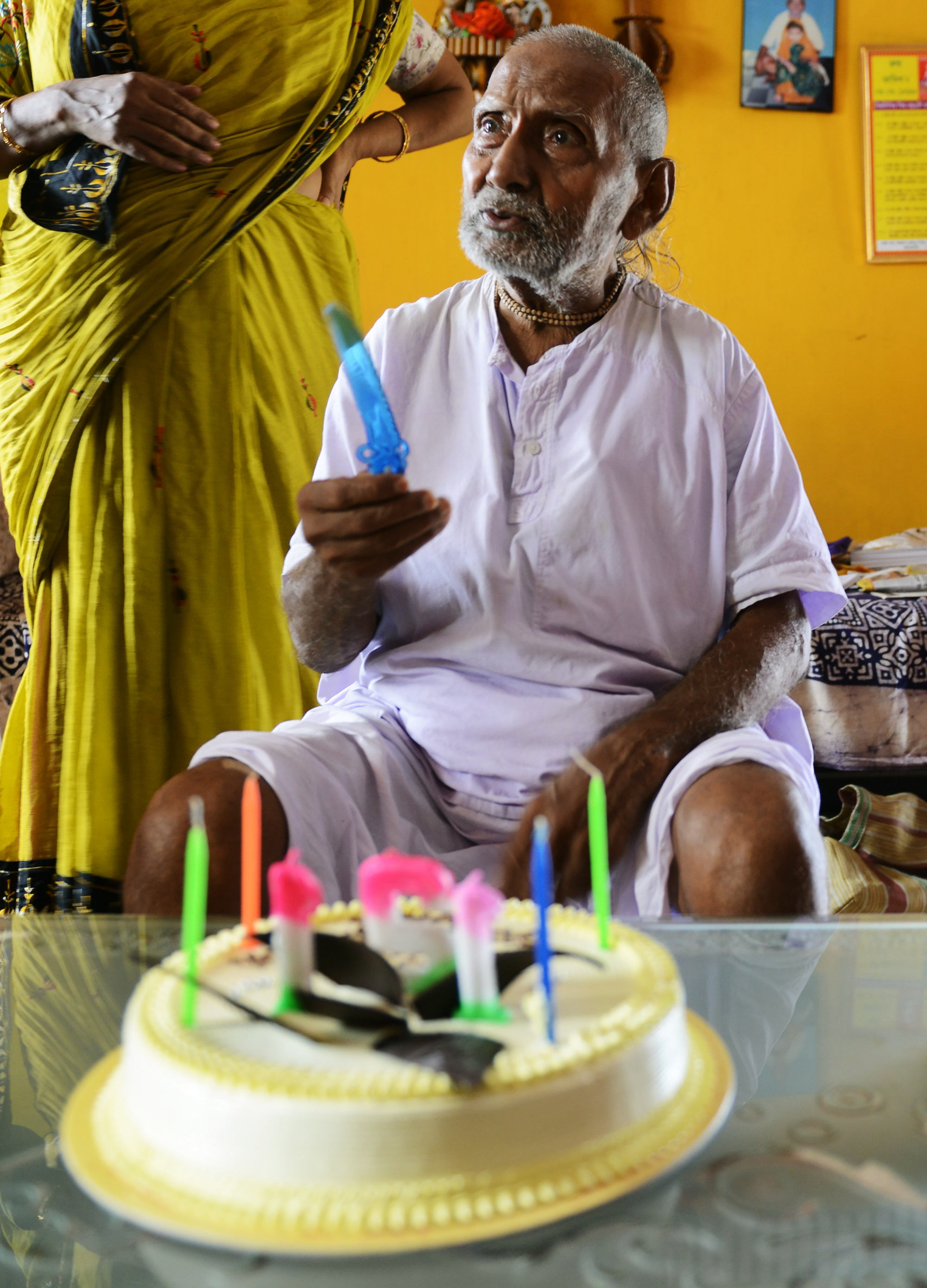 In this photograph taken on August 2, 2016, Indian monk Swami Sivananda reacts after his followers presented him with a birthday cake in Kolkata. An Indian monk who claims to be the oldest man to have ever lived at 120 years, says he owes his longevity to daily yoga and a life without sex or spices. Born on August 8, 1896, according to his passport, Hindu monk Swami Sivananda's life has spanned three centuries. He is now applying to Guinness World Records to stake his claim to the distinction. / AFP PHOTO / Dibyangshu SARKAR / TO GO WITH AFP STORY: ' India-Lifestyle-Oldest-Man' Feature by Dibyangshu SARKAR