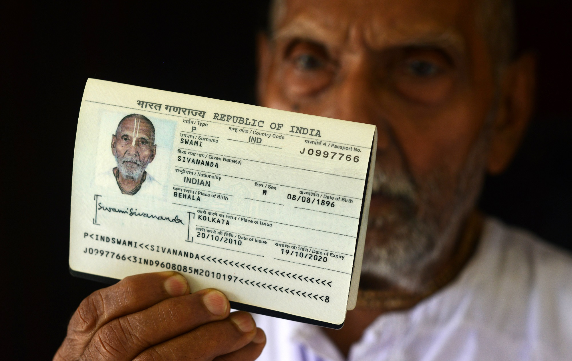 In this photograph taken on August 2, 2016, Indian monk Swami Sivananda, who claims to be 120 years old, holds up his passport in the house of one of his followers in Kolkata. An Indian monk who claims to be the oldest man to have ever lived at 120 years, says he owes his longevity to daily yoga and a life without sex or spices. Born on August 8, 1896, according to his passport, Hindu monk Swami Sivananda's life has spanned three centuries. He is now applying to Guinness World Records to stake his claim to the distinction. / AFP PHOTO / Dibyangshu SARKAR / TO GO WITH AFP STORY: ' India-Lifestyle-Oldest-Man' Feature by Dibyangshu SARKAR