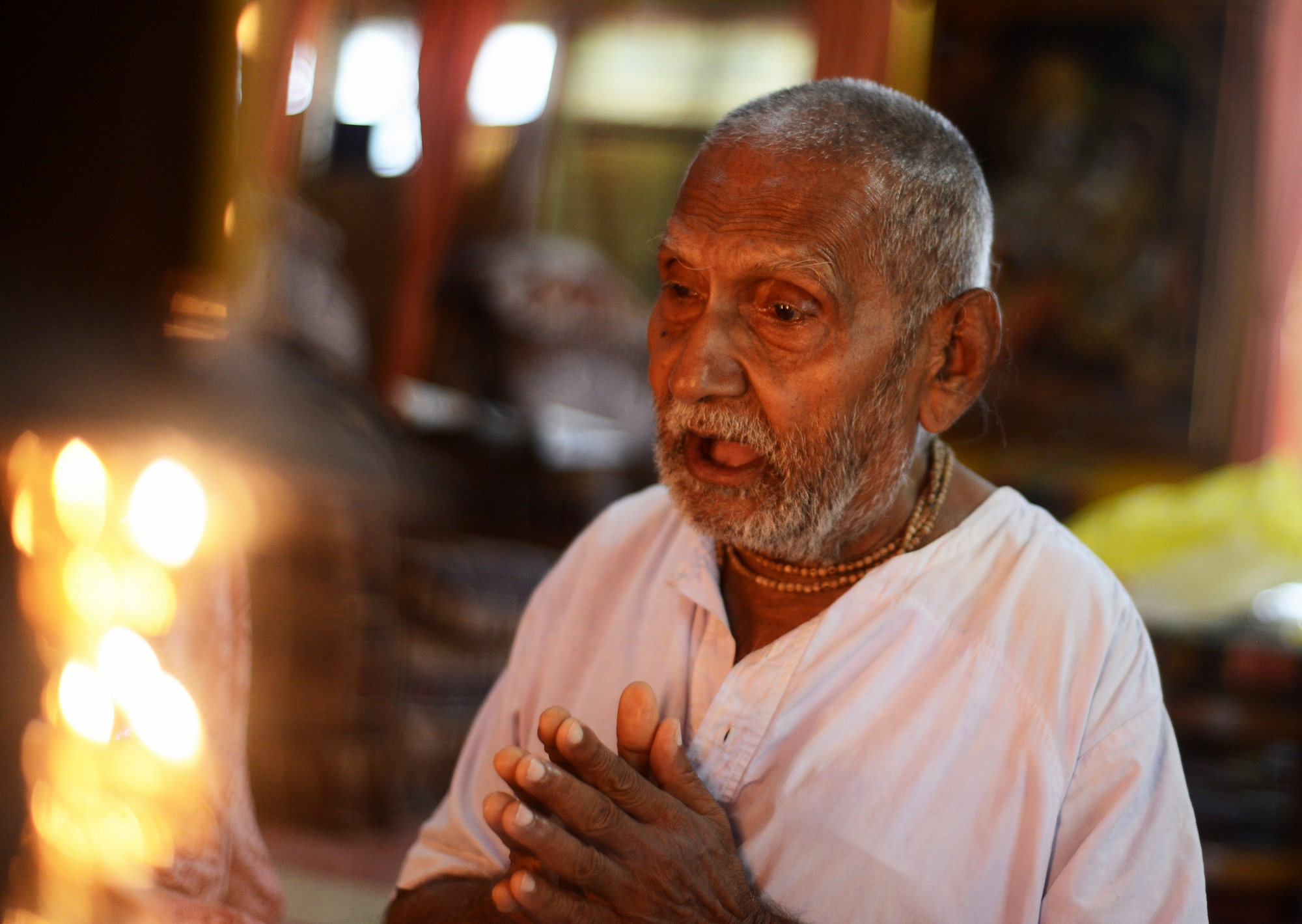 In this photograph taken on August 2, 2016, Indian monk Swami Sivananda, who claims to be 120 years old, prays ahead of performing his morning stretches and yoga in Kolkata. An Indian monk who claims to be the oldest man to have ever lived at 120 years, says he owes his longevity to daily yoga and a life without sex or spices. Born on August 8, 1896, according to his passport, Hindu monk Swami Sivananda's life has spanned three centuries. He is now applying to Guinness World Records to stake his claim to the distinction. / AFP PHOTO / Dibyangshu SARKAR / TO GO WITH AFP STORY: ' India-Lifestyle-Oldest-Man' Feature by Dibyangshu SARKAR
